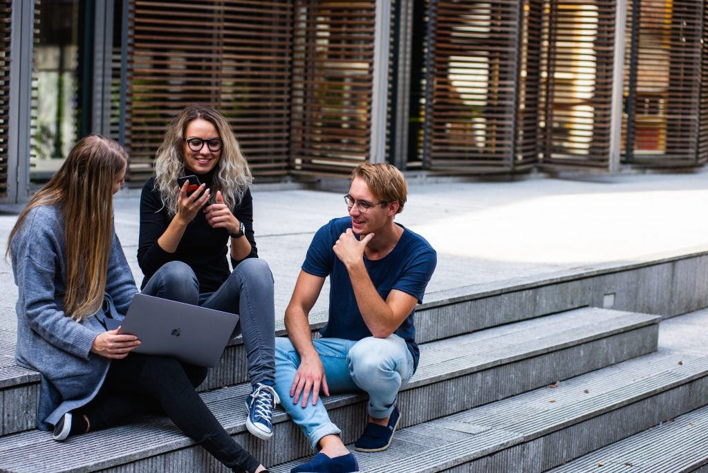 three-persons-sitting-on-the-stairs-talking-with-each-other-1438072